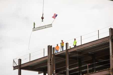 "Construction crews guide the ""topping off"" white steel beam into place on the Health System's new Inpatient Tower."